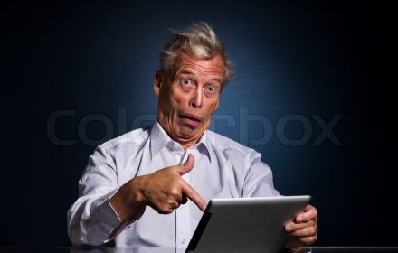 8145679-shocked-senior-man-pointing-to-his-tablet